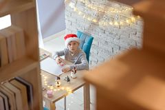 Child in Santa Claus cap drawing a pastel drawing for Santa Claus. Or writing a wish list stock photography