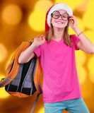 Child with Santa Claus red hat, backpack and glasses on bright background Stock Image