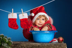 Child in Santa hat. Washing in basin. Christmas concept Royalty Free Stock Images