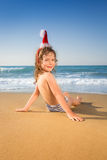 Child in Santa hat at the beach Royalty Free Stock Image