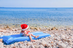 Child in Santa hat on the beach Stock Image