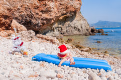 Child in Santa hat on the beach Royalty Free Stock Images