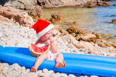 Child in Santa hat on the beach Royalty Free Stock Photography