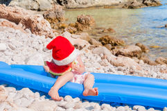 Child in Santa hat on the beach Stock Photo