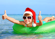 Child in santa hat  floating on inflatable ring. Royalty Free Stock Photos