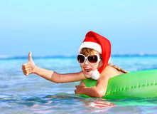 Child in santa hat  floating on inflatable ring in sea. Thumb up Royalty Free Stock Image