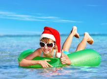 Child in Santa hat  floating at  sea. Child in Santa hat  floating on inflatable ring in sea. Thumb up Royalty Free Stock Image