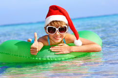 Child in santa hat floating at sea. Child in santa hat floating on inflatable ring in sea. Thumb up Royalty Free Stock Images