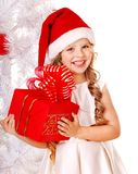 Child in Santa hat with gift box. Child in Santa hat with gift box near white Christmas tree. Isolated Royalty Free Stock Photos