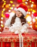 Child in Santa hat with gift box. Child in Santa hat with big red gift box Royalty Free Stock Images