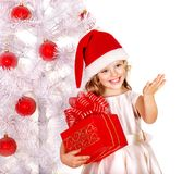 Child in Santa hat with gift box near white Christmas tree. Isolated Stock Photography