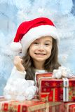Child in Santa hat with gift box. Child in Santa hat with gift box near white fir-tree Royalty Free Stock Photo