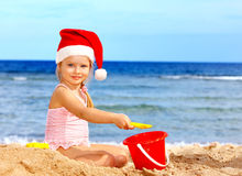 Child in santa hat playing on  beach. Royalty Free Stock Image