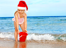 Child in santa hat playing on  beach. Royalty Free Stock Images
