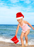 Child in santa hat playing on beach. Summer New Year Royalty Free Stock Image