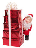Child in santa hat by stack gift box. Stock Images