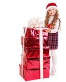 Child in Santa hat with stack gift box. Stock Photos