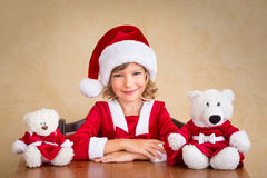 Child in Santa hat with teddy bear Royalty Free Stock Photos