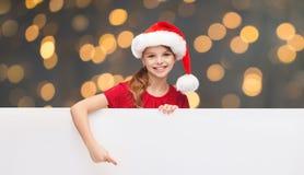 Child in santa helper hat with blank white board Stock Photo