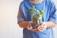 Child saving money in Bottle money growing up as tree. Child saving money in Bottle money growing up as tree Stock Photography