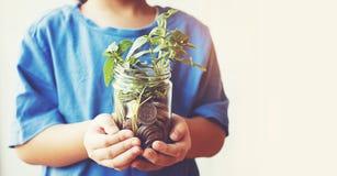 Child saving money in Bottle money growing up as tree stock image