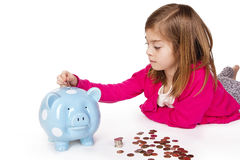 Child Saving money in a piggybank. A child placing money into a blue piggybank. Isolated on a white background Stock Image