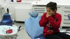Child scared when looking on the dental tools at dental clinic. Girl dressed in a christmas pullover. Young patient lies at dental chair royalty free stock photos