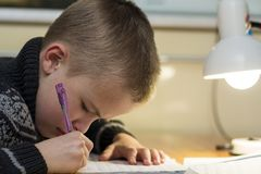 Child school age boy making his homework.  Stock Photos