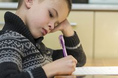 Child school age boy making his homework.  royalty free stock photo