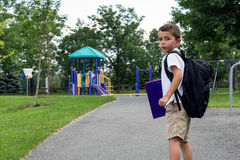 Child with school backpack and book walking in the park Royalty Free Stock Photo