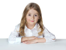 Child school girl isolated on white sit at table. Royalty Free Stock Photo