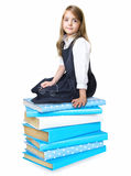 Child school girl sitting on stack pile of books isolated. Stock Image