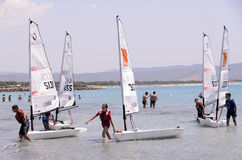 Child school sailing in sardinia. The school sailing in the south of Sardinia. In the Gulf of Porto Pino in the south of Sardinia young boys studying the wind Royalty Free Stock Photo
