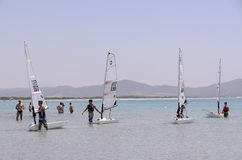 Child school sailing in sardinia. The school sailing in the south of Sardinia. In the Gulf of Porto Pino in the south of Sardinia young boys studying the wind Stock Image