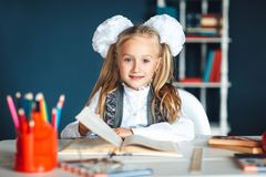 Child and school supplies home Schoolgirl at the table with a textbook and colorful stationery. Girl in school uniform at a Desk stock image