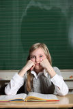 Child in the school thinks. One child sits with a book in front of a blackboard at school and thinks Royalty Free Stock Photos
