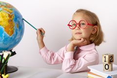 Cute industrious child is sitting at a desk indoors. stock images