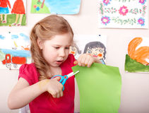 Child with scissors cut paper at home. Stock Image