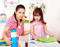 Child with scissors cut paper in play room. Stock Images