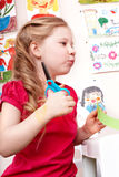 Child with scissors cut paper in play room. Royalty Free Stock Photography