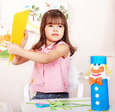 Child with scissors cut paper in preschool. Royalty Free Stock Images
