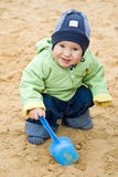 Child with a scoop in a sandbox. Child with a blue scoop in a sandbox Royalty Free Stock Image