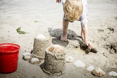 Child on Beach Builds Sand Castles with a Red Bucket. A child scoops up water from a sandy beach with a shell while building a two tower sand castle decorated royalty free stock photos