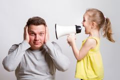 Child in a megaphone parent. Child screaming with megaphone to adult indifferent man Royalty Free Stock Images