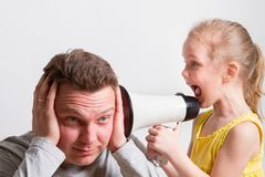 Child in a megaphone parent. Child screaming with megaphone to adult indifferent man Royalty Free Stock Photos