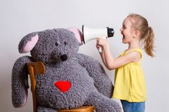 Child screaming into a megaphone. Child screams into a megaphone for a big mouse toy Stock Image