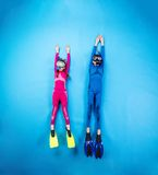 Child scuba divers. Children scuba diving deep in the sea. Studio shot on a blue background Stock Images
