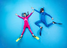 Child scuba divers. Children scuba diving deep in the sea. Studio shot on a blue background royalty free stock photos
