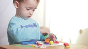 The child sculpts figures from plasticine sitting at the table at home. Child development stock footage