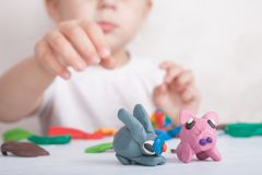 Child sculpts from plasticine pig and bunny stock image